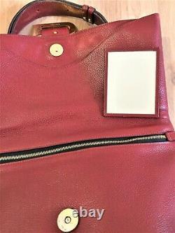 Delvaux Bruxelles Sac besace vintage en cuir couleur bordeaux porté main épaule